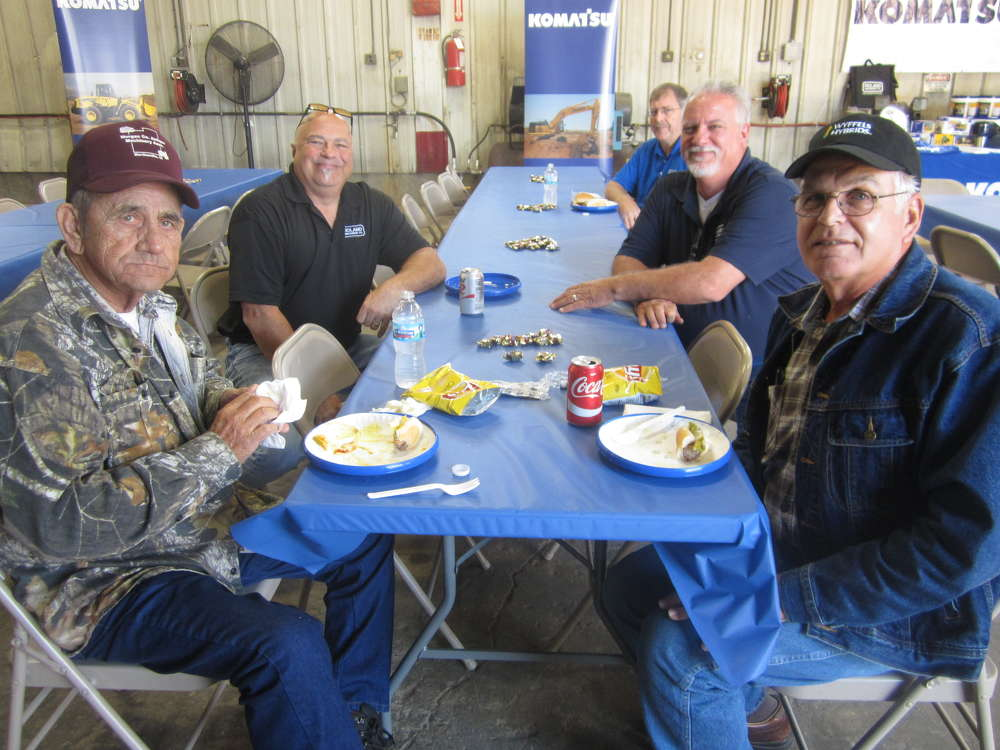 Wayne Counterman (front L) and Keith Keller (front R), both of Elm Grove Township; Mark Lynn (middle L) and Mike Martin (middle R), both of Roland Machinery Co.; and Steve Germann (back R), Roland Machinery, take a few minutes to grab a bite.