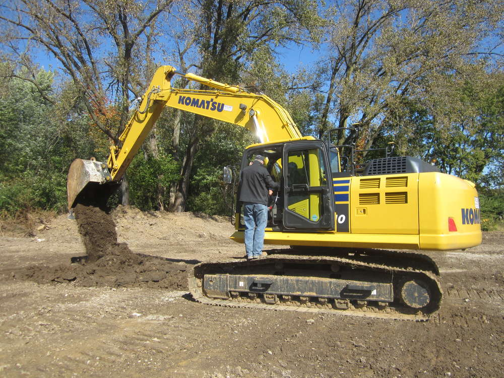 Customers operate this Komatsu PC210LCi excavator at the open house.