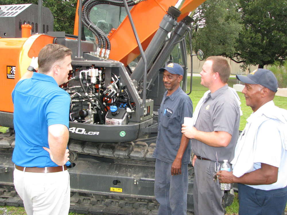 (L-R): Adam Howard of Doosan goes over the features of this Doosan DX140LCR excavator with Anthony Javis, Cody Allen and Jerry Hales, all of the city of Pooler, Ga.