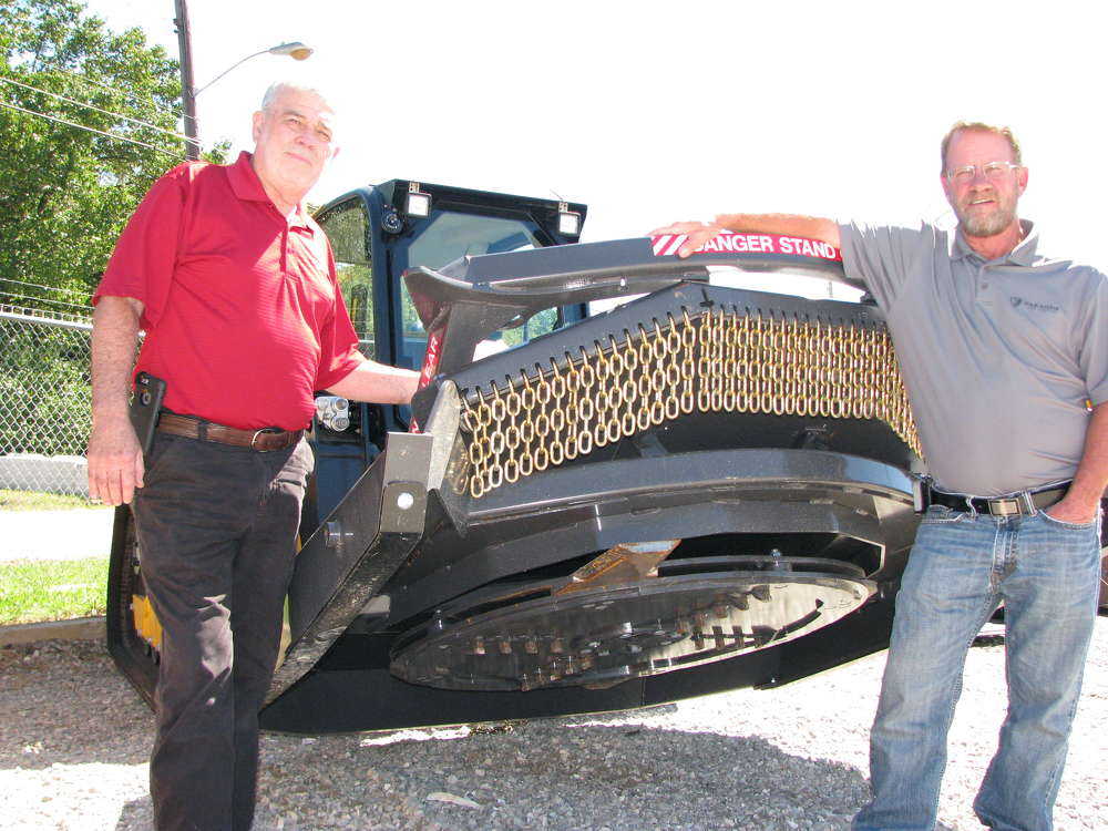 Jim Myers (L) and Marty Owen, both of Paladin, answer questions about the selection of skid steer and compact track loader attachments on display, including this Paladin-Bradco Ground Shark heavy-duty brush cutter.