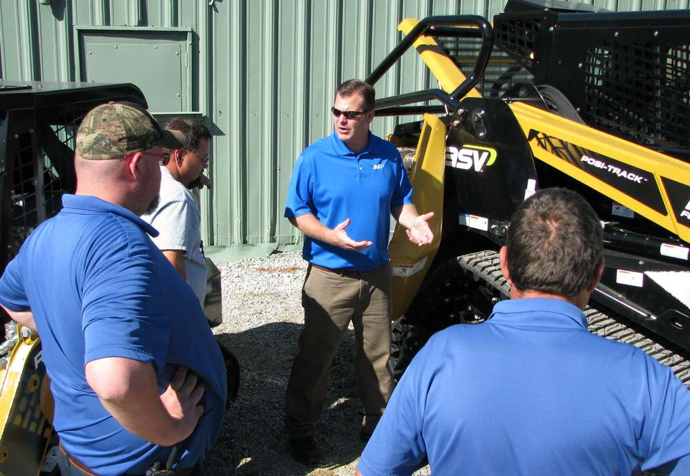 Matt Sawyer (C), ASV factory representative, Grand Rapids, Minn., gives guests a comprehensive walk around of an ASV RT120 compact track loader with forestry package.