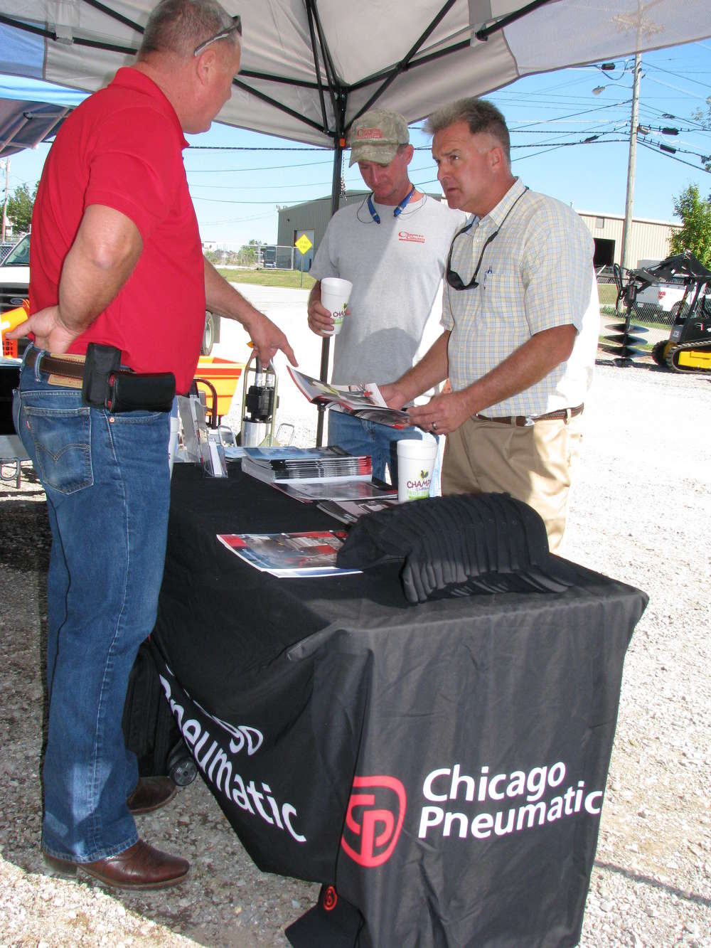 (L-R): Eric Massinon of Chicago Pneumatic, Indianapolis, Ind., fields questions from Larry Allen and Greg Chapman, both of Chapman Concrete Construction, Chattanooga, Tenn., about the company's products.
