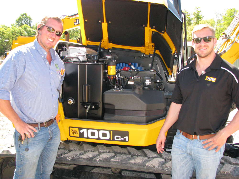 Andrew Presswood (L), Presswood Construction, Cleveland, Tenn., and David Barker, JCB retail sales manager, based in Atlanta, Ga., inspect the engine of this JCB 100 C-1 mini-excavator.