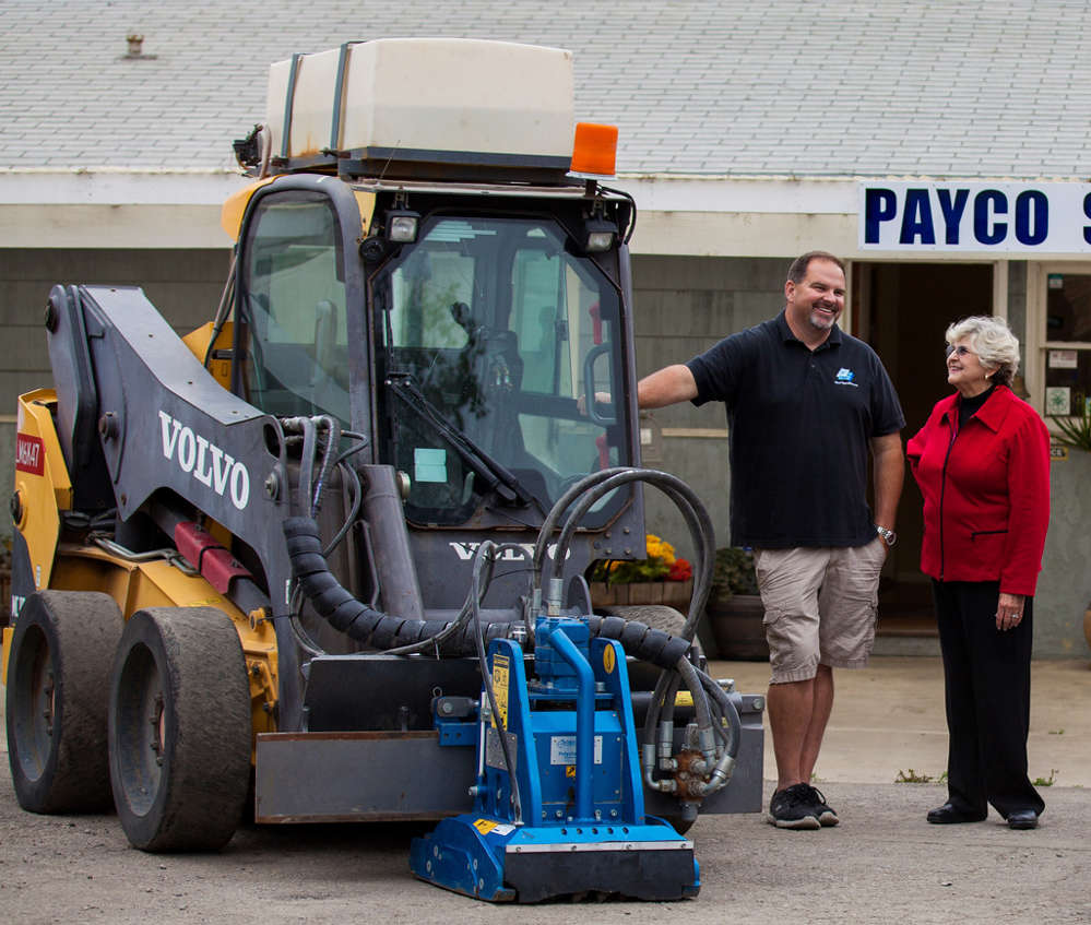 Mother and son, Rebecca (R) and Jeff Llewellyn, stand beside the Volvo MC115C skid steer loader.