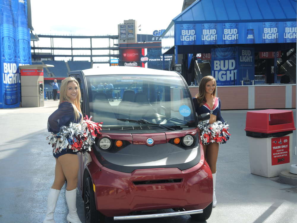 New England Patriot cheerleaders took a picture with the Polaris Gem electric car.