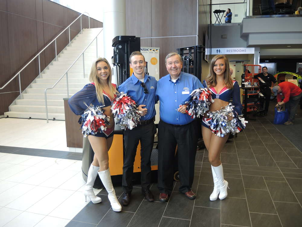 Patrick Maclean (L), Northland JCB sales representative and Steve O'Leary (R), president of NITCO, were happy to get a picture with two New England Patriot cheerleaders.