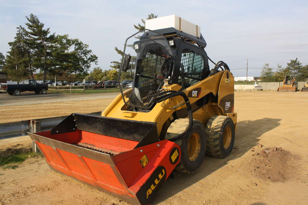 This Cat 246C skid steer stands ready to demonstrate the abilities of the ALLU DL screening bucket.