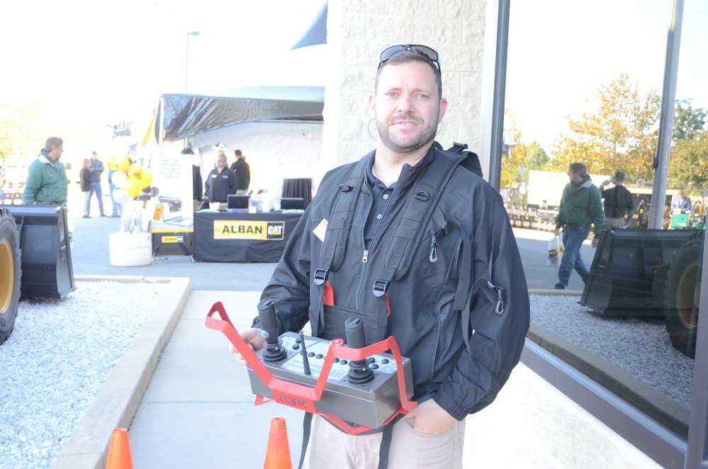 Steve Price, rentals sales representative of Alban CAT, demonstrates the Remote Task Skid Steer handheld remote on a Caterpillar 2990 skid steer.