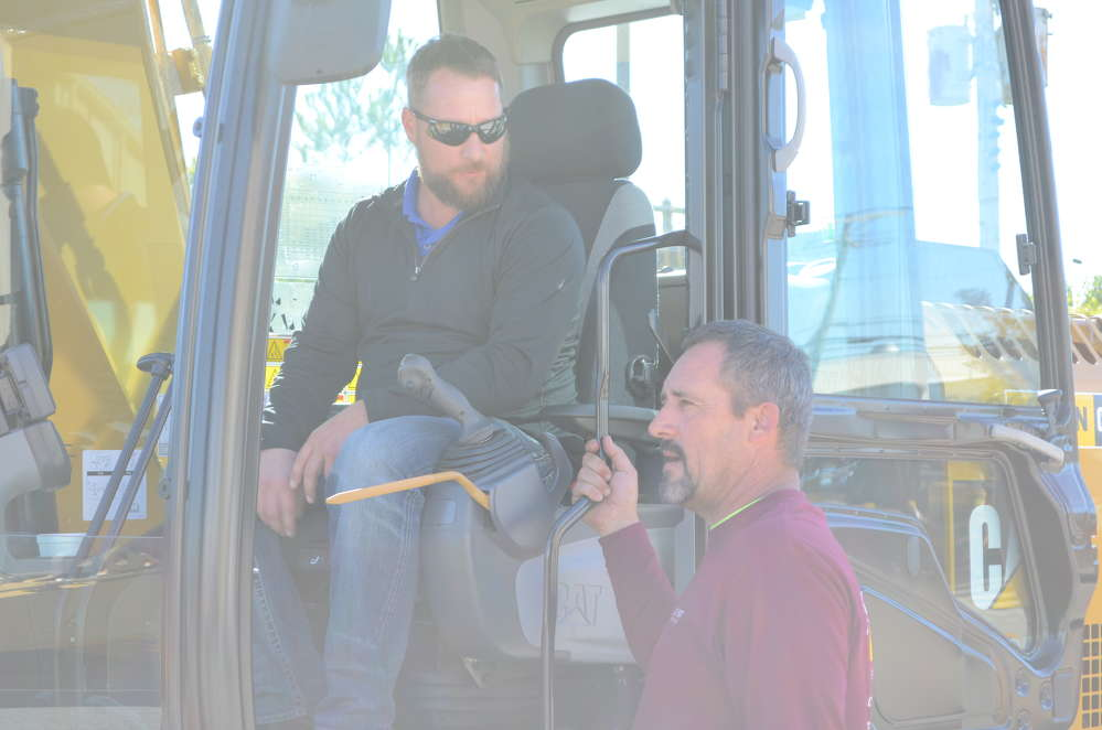 Gerry Mallory (in cab), general manager of Rototilt, speaks with Kevin Martin of Love Point Ventures in Stevensville, Md.