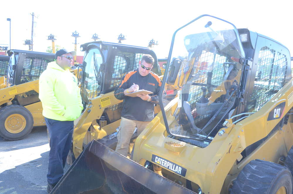 David Oliphant (L), owner of Mow Blow & Go Outdoor Services in Perry Hall, Md., purchased a skid steer from Chris Redding of Alban CAT.