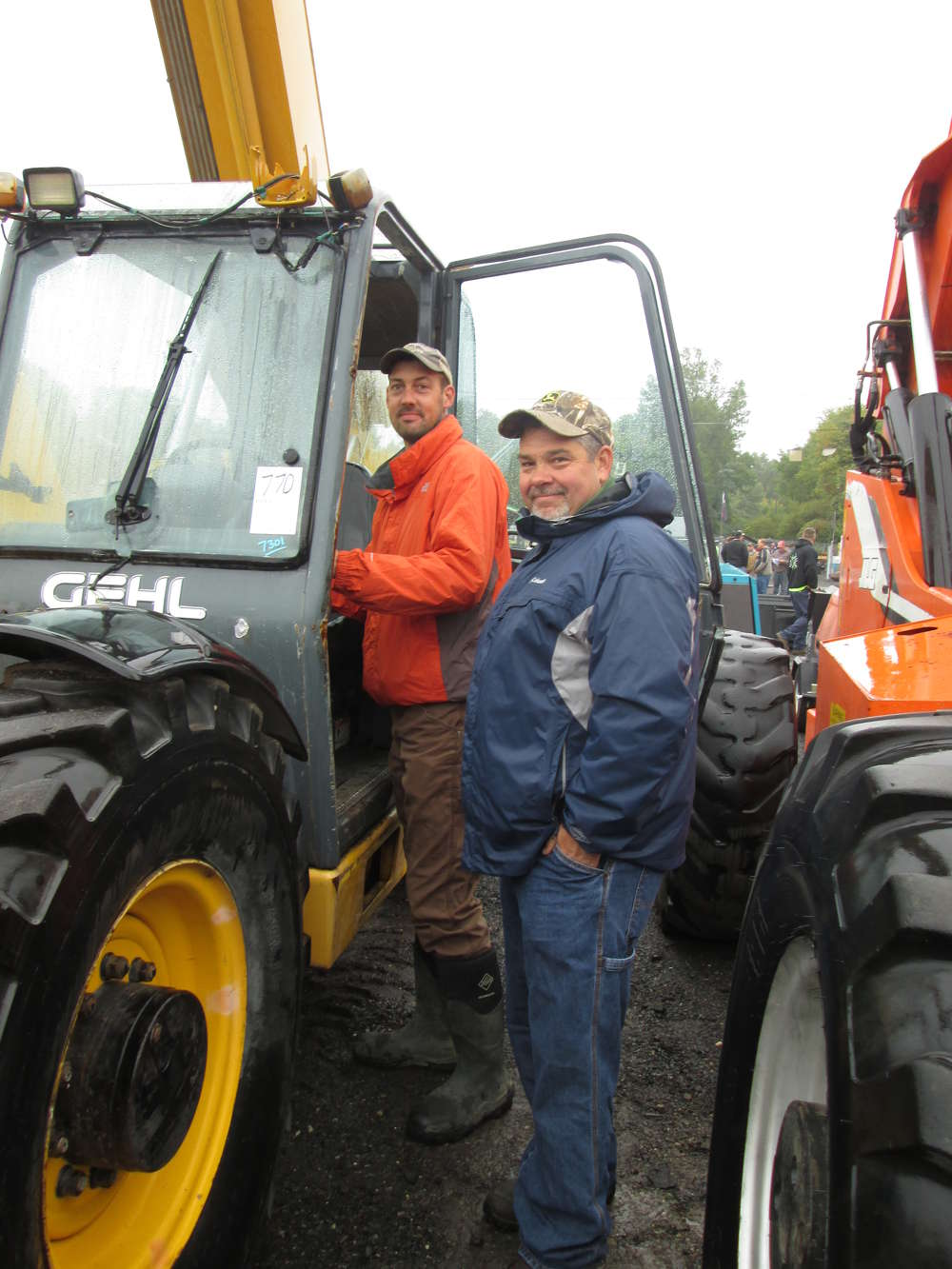 Steve Carroll (R) and his cousin, Marc Astrella, of Carroll Custom Contracting, West Brookfield, Mass., check out a Gehl telehandler/boom truck.