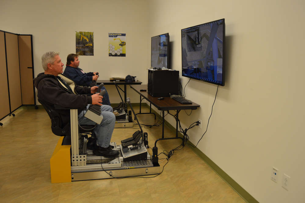 Martin James (L) and Matt Dunn, both of Local 14, use the excavator simulator at the Local 14 training facility.