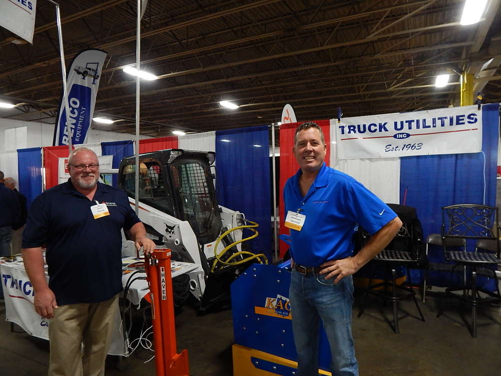 Dan Reetz (L), territory manager of Shaver, holds a post pole attachment at the Truck Utilities booth while talking to Charlie Miller, sales engineer, Truck Utilities, St. Paul, Minn.
