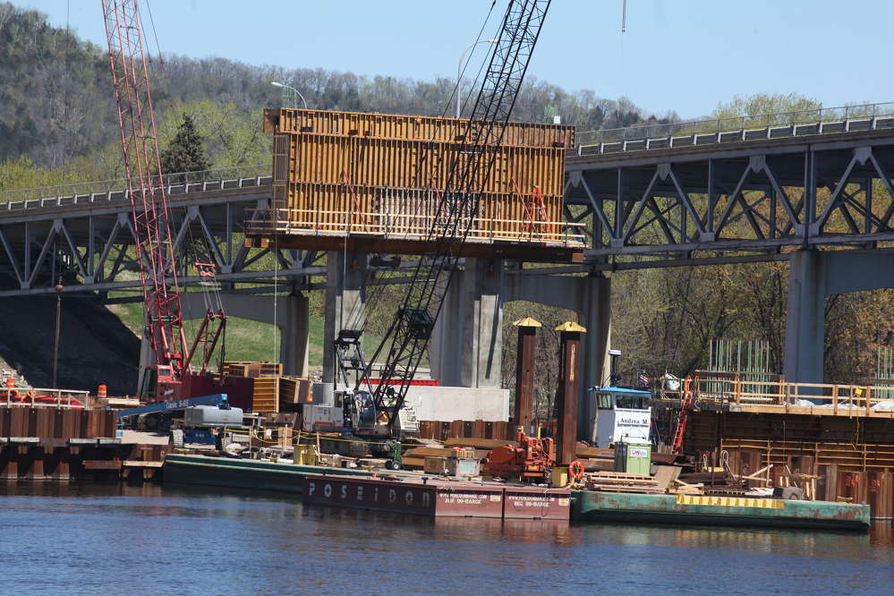 Two cranes, a Terex and Manitowoc are stationed near one of three river piers rising above the river. Bridge crews worked through the winter of 2014/2015 to build the piers above possible spring 2015 flood levels.