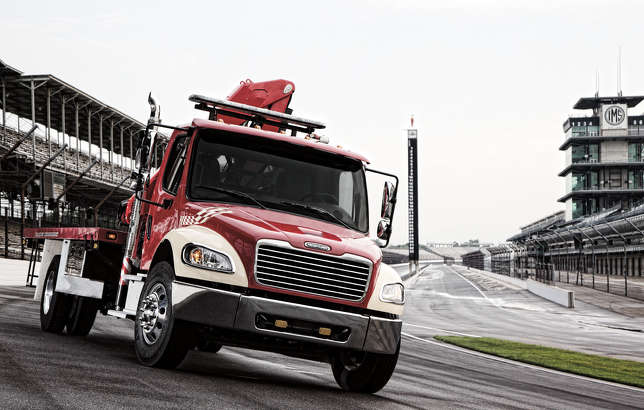 Freightliner trucks pitch in at racing events by clearing track of debris, safely removing wrecked cars from the track and moving TV production and hospitality equipment from track to track.