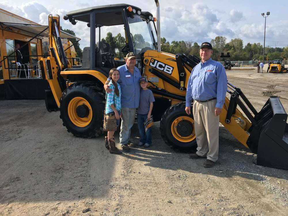 Neil Williams (R) of Company Wrench goes over the JCB 3CX backhoe with George, Katie and Cana Wilson of Wilson Farm in Kershaw, S.C.