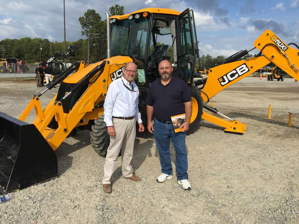 Ken Hanna (R), Hanna Farms in Lake City, S.C., currently owns a JCB backhoe and asks Billy Wall of Company Wrench about other items in the JCB product line.