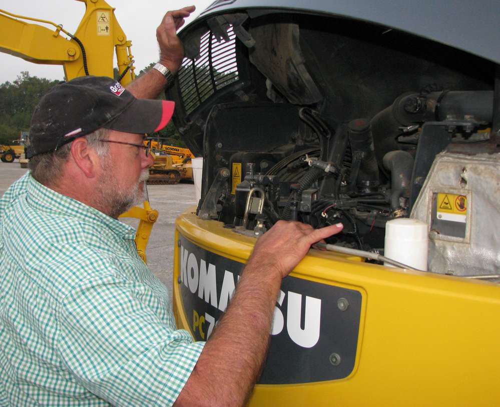 Herbert Hare, Hare Tractor, Cullman, Ala., checks the engine of a Komatsu PC78mr mini-excavator.