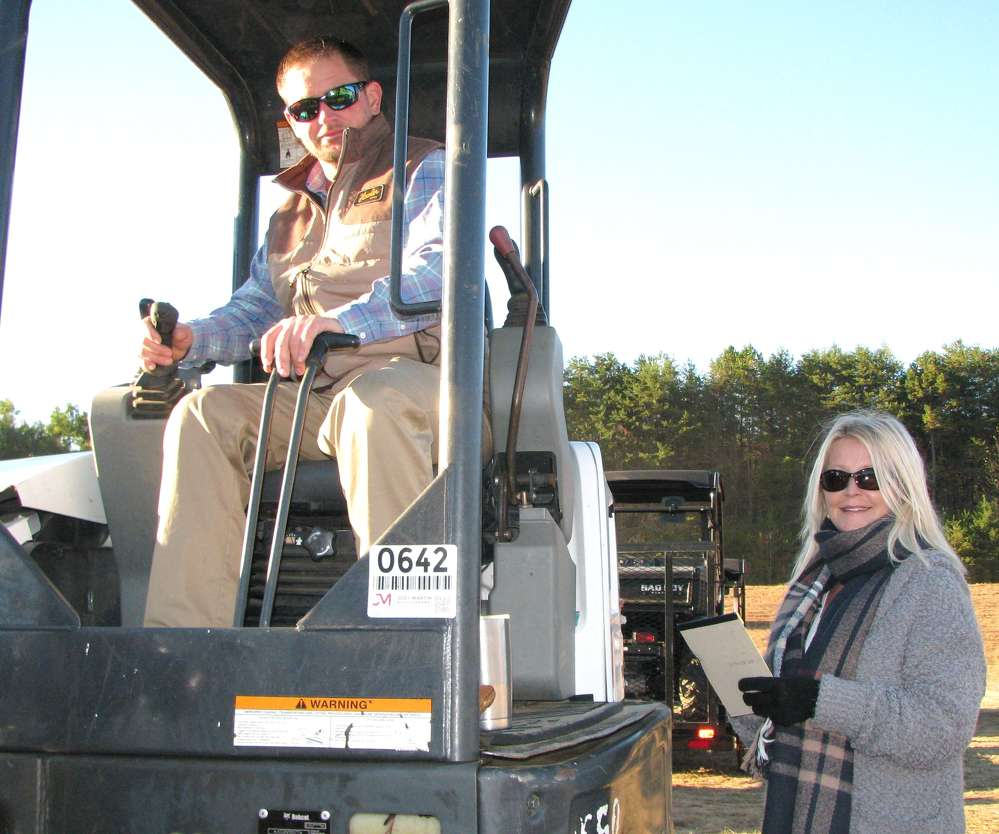 Toby and Kim Adams of Adams Equipment, Buchannan, Ga., look over some of the mini-excavators about to go on the auction block.