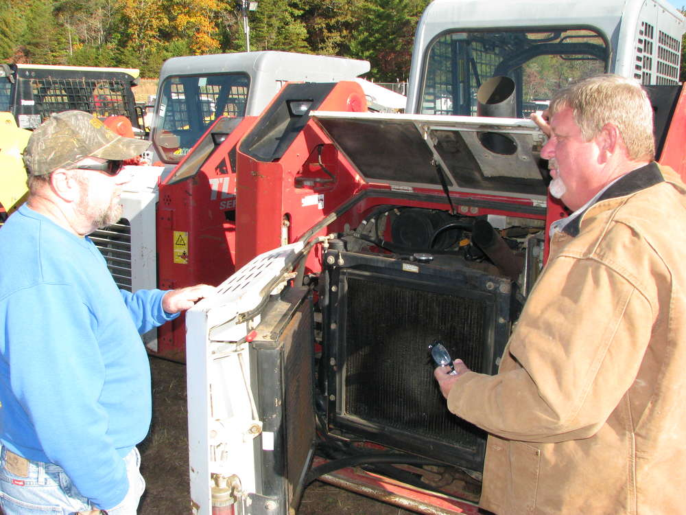 Leroy Dishman (L) and Randy Saxon of D&A Enterprises, Dewy Rose, Ga., inspect this Takeuchi compact track loader.