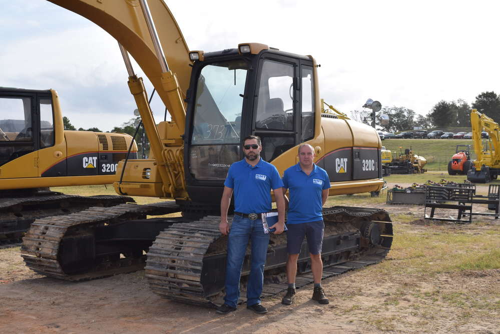 Kevin Skoglund (L), St. Pete, Fla., and Shaun Dunning, United Kingdom, both of MT Shipping, look at this Cat 320.