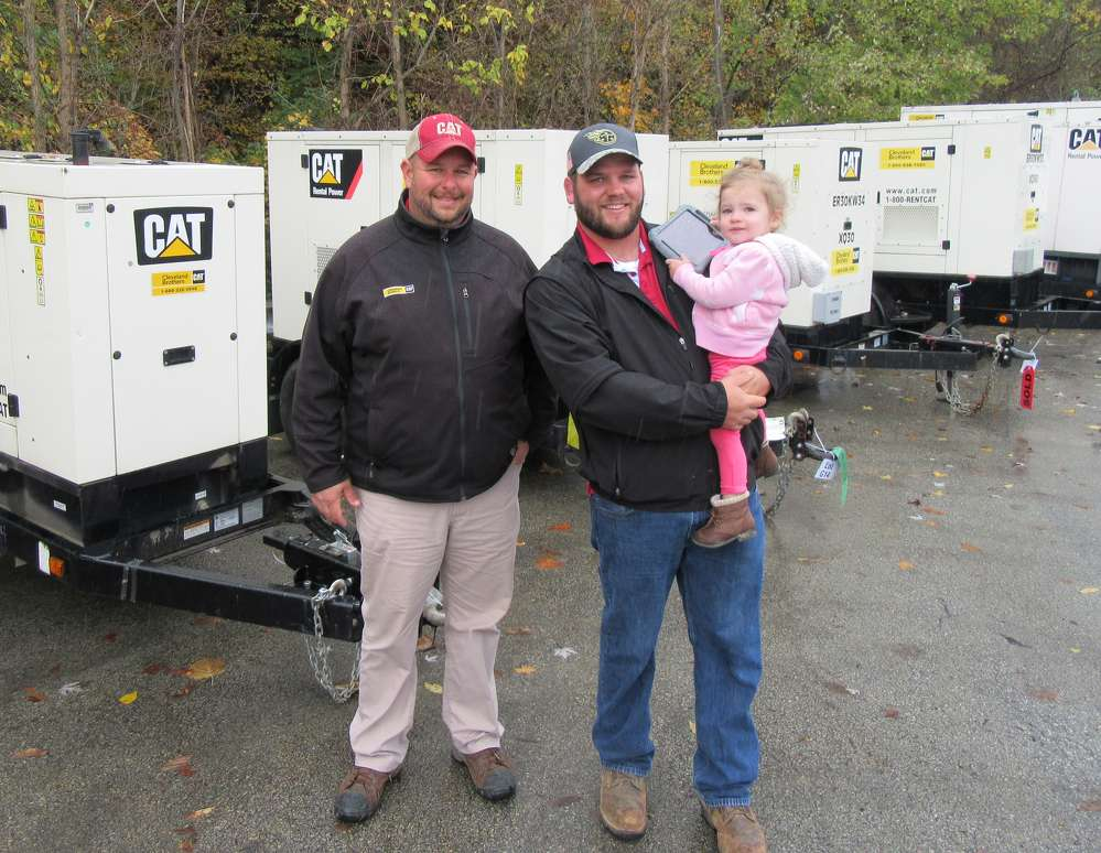 Mike Jones (L) of Cleveland Brothers walked A.J. Brentzel  of A.J. Brentzel  Excavation & Services and Brentzel's daughter, Blaire, through the lineup of equipment on sale.
