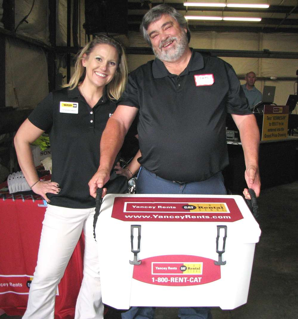 Amanda Hague, Yancey Bros. Co., presents another prize winner, Charles Waters of the city of Roswell, Ga., with a Grizzly cooler packed with goodies.