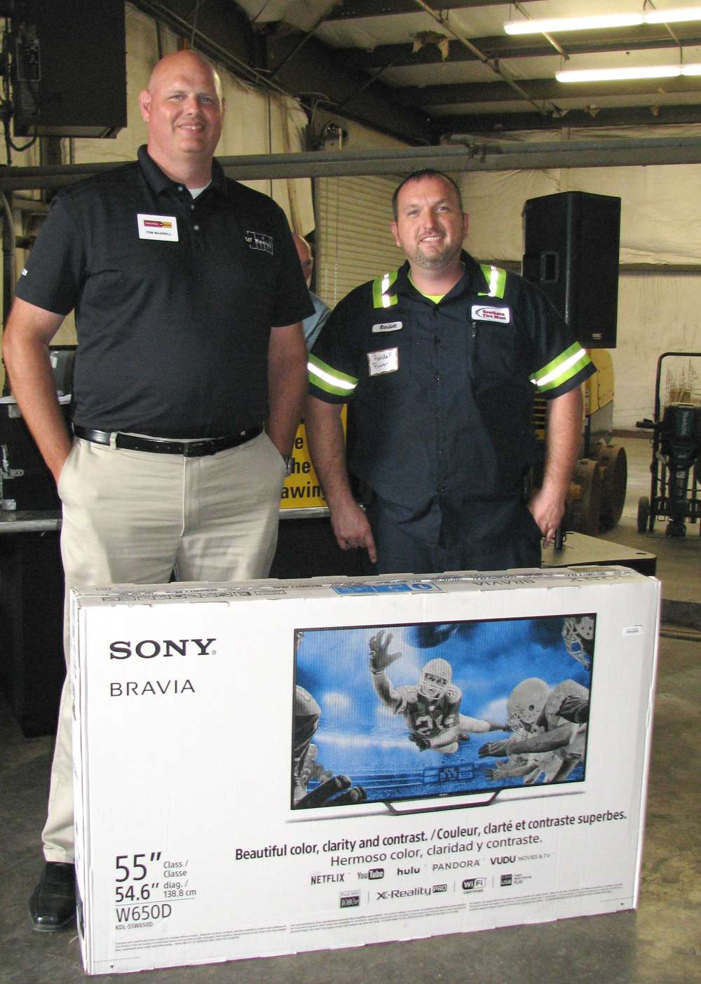 Tom Maxwell (L), Yancey Rents rental operations manager, presents the final grand prize of the day, another 55-in. Sony TV, to Randall Rowan of Southern Tire Mart, Atlanta, Ga.