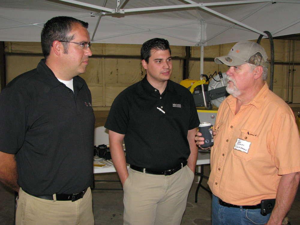(L-R): Brent Yarbrough and Matt Brooksher of Wacker Neuson talk to one of their regular customers, Tom Sizemore of C.W. Matthews Contracting, Marietta, Ga.