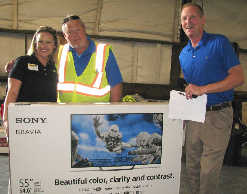 Michael Anthony Cochran (C) of Baldwin Paving, Marietta, Ga., stopped in for lunch was a grand prize winner of a 55-in. Sony TV. Presenting him with the prize are Yancey Bros. Co.'s Amanda Hague and Ron Mundy event emcee.