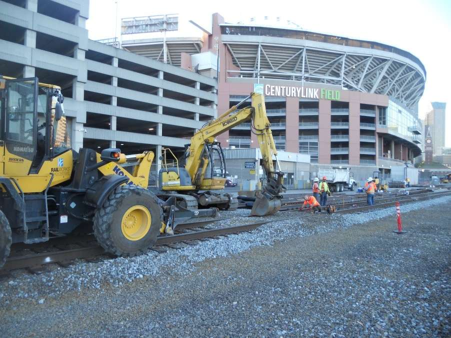 WSDOT photo. A Komatsu WA320 wheel loader (foreground) and a Kobelco 175 excavator are two of the workhorses involved in replacing hand-operated switches with automatic switches at King Street Station in Seattle.