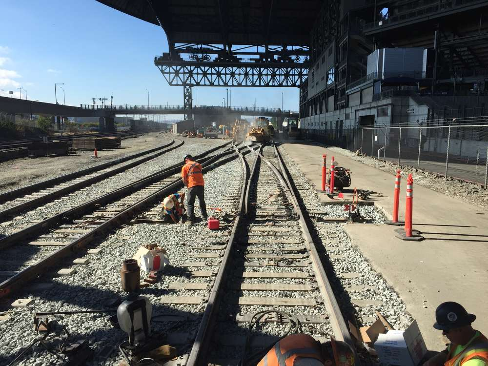 RailWorks photo.  The King Street Station tracks run directly behind Safeco Field and CenturyLink Field.  Workers labor on a double crossover switch in the shadow of the Safeco Field retractable roof.