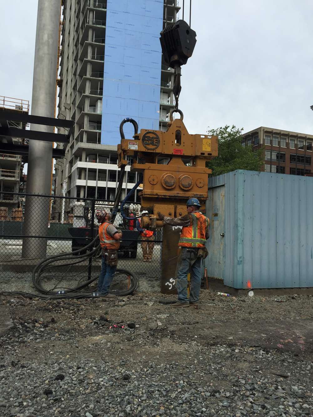 Granite Construction photo. A pile nears the end of its journey as workers keep a close eye on the APE 150 vibratory hammer.