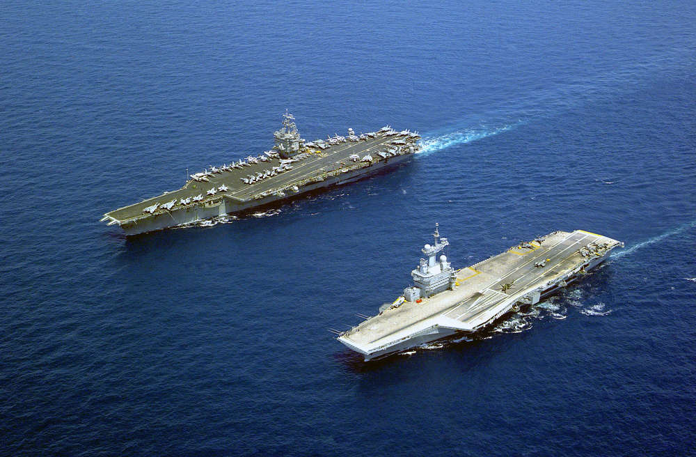 The U.S. Navy aircraft carrier USS Enterprise (CVN-65), the world's first nuclear-powered aircraft carrier, steams alongside the French aircraft carrier Charles De Gaulle (R 91). Enterprise and her battle group were on a scheduled deployment in the Mediterranean Sea.