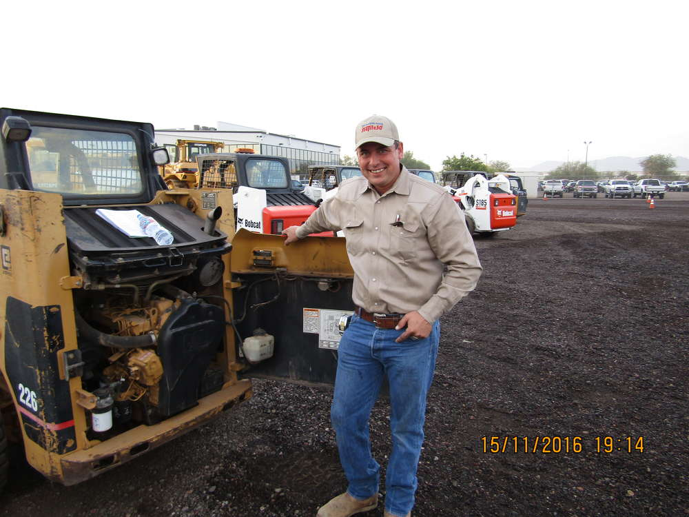 Ephraim Balo of Balo Ranch, Skull Valley, Ariz., who plans to buy skid steers and backhoes for the ranch, looks over this Cat 226 skid steer.