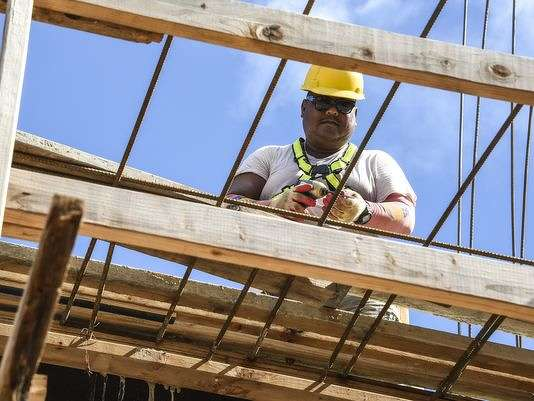 Carpenter Negs Barrozo prepares to fasten lumber together into a form, as he and other 5M Construction Corporation employees, work at a building project in Tamuning on Tuesday, Oct. 4. (Pacific Daily News photo)