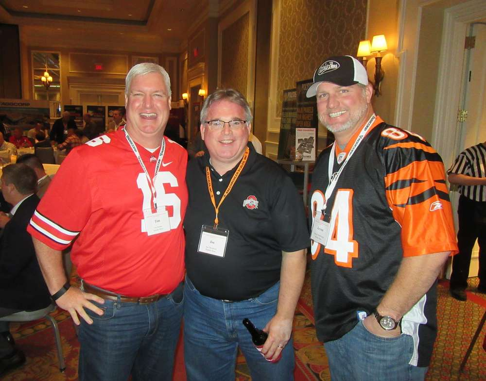 (L-R): Tim Keane, Joe Dombeck and Jayson Hutchinson, all of Ritchie Bros., dress in their favorite sports team gear for the OAIMA tailgate party.