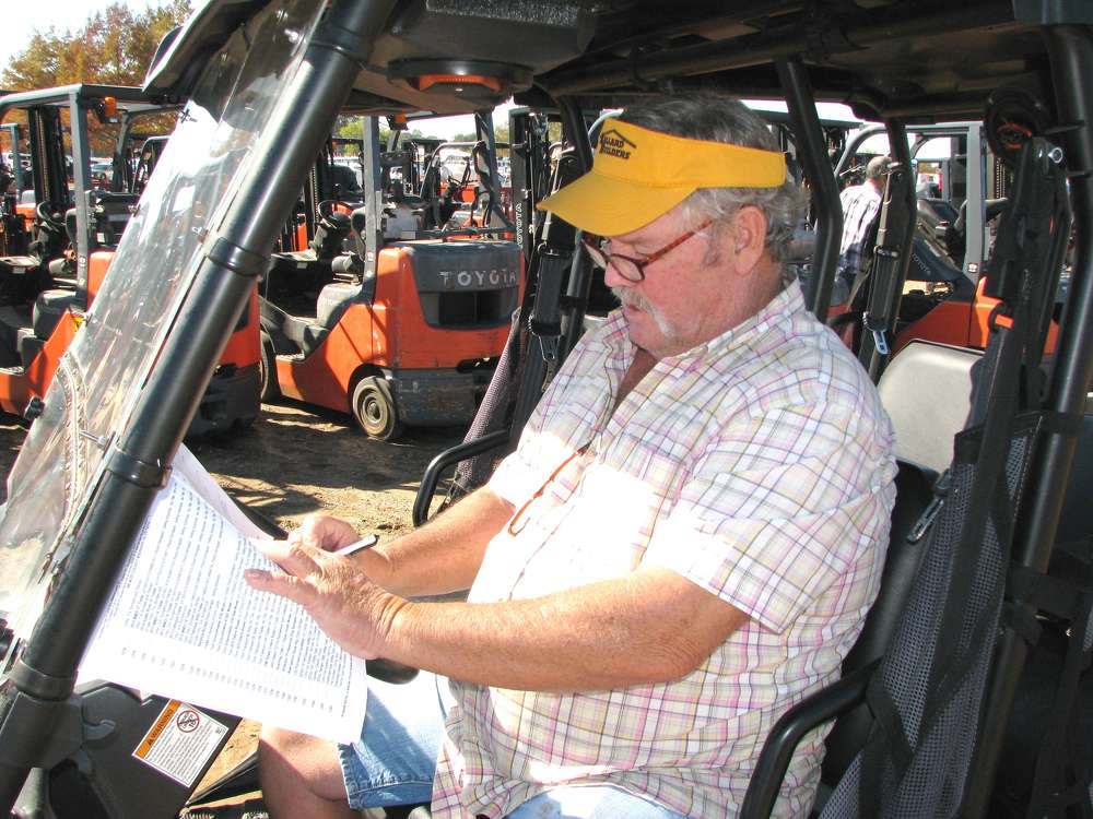 Warren Ballard, Ballard Builders, based in Winfield, Ala., jots down final notes on forklifts and skid steer loaders of interest.