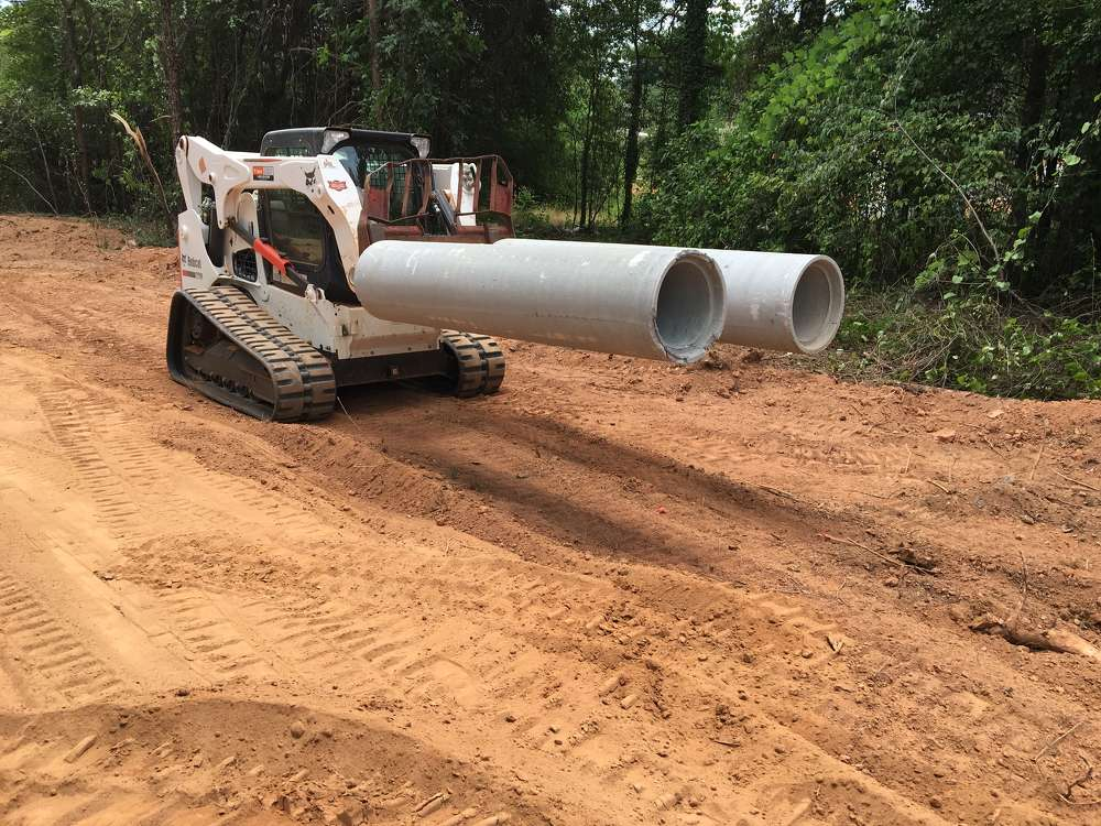 The operator of the Bobcat T770 uses forks to move the pipe.