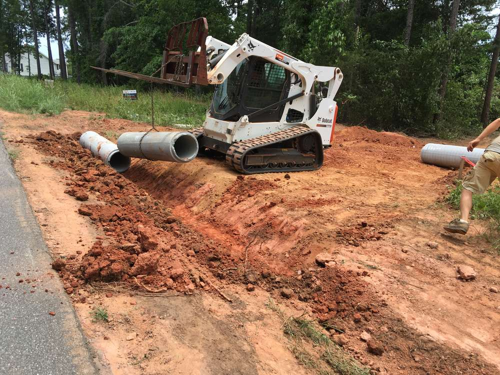 he operator of the Bobcat T770 sets the pipe after digging the ditch.