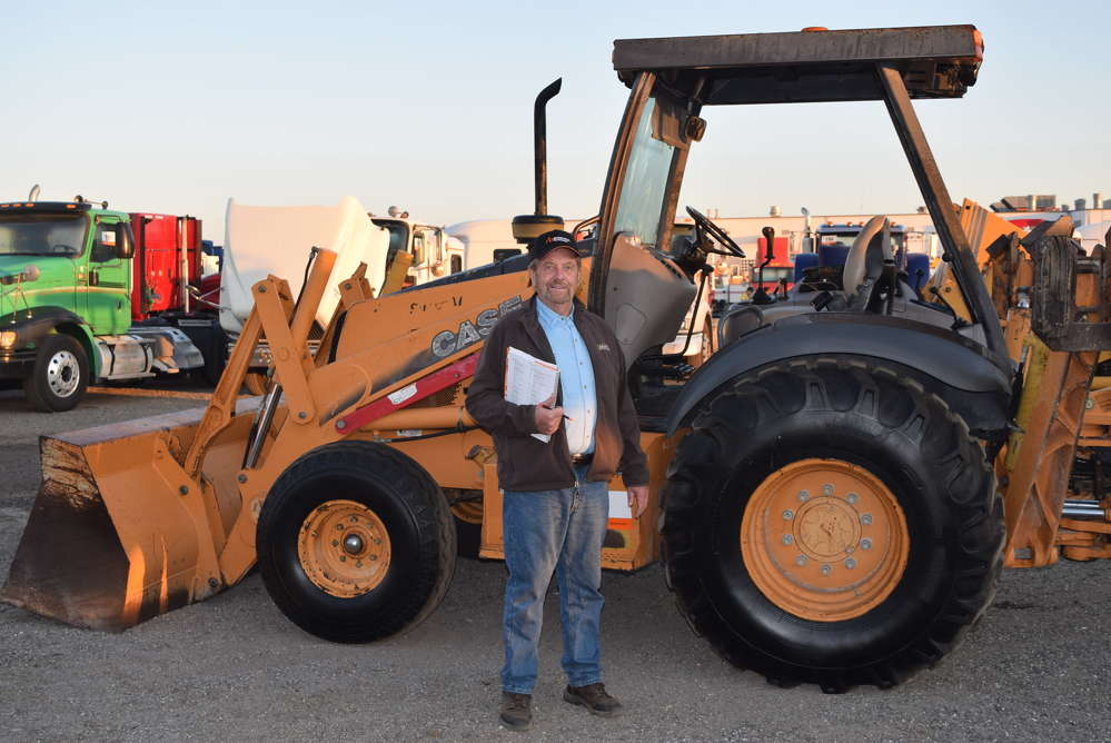 Gary Gray, Gray Trucking, Delaware Township, N.J., inspects this Case backhoe excavator before the start of the auction.