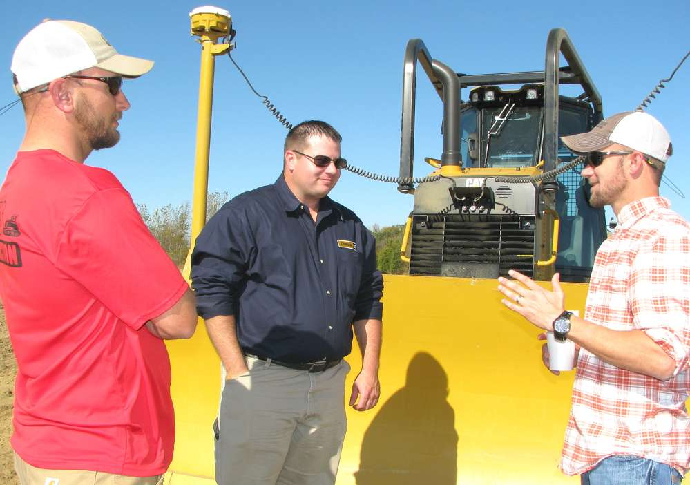 (L-R): Adam Stubblefield, AHS Construction, Pontotoc, Miss.; Bruce Thomas, Thompson Machinery; and Don Kelly Stewart, Eutaw Construction, Aberdeen, Miss., talk about the Cat D6K2 dozer with grade control and add on Accugrade system.