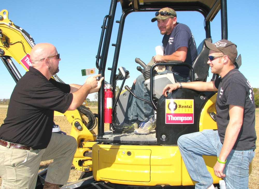 (L-R): Casey Clayton, Thompson Machinery CAT Rental Store representative, speaks with Matt Free and Dustin Murphree, both of Lackey's Electrical, Tupelo, Miss., about the features of this Cat 304e2 CR.