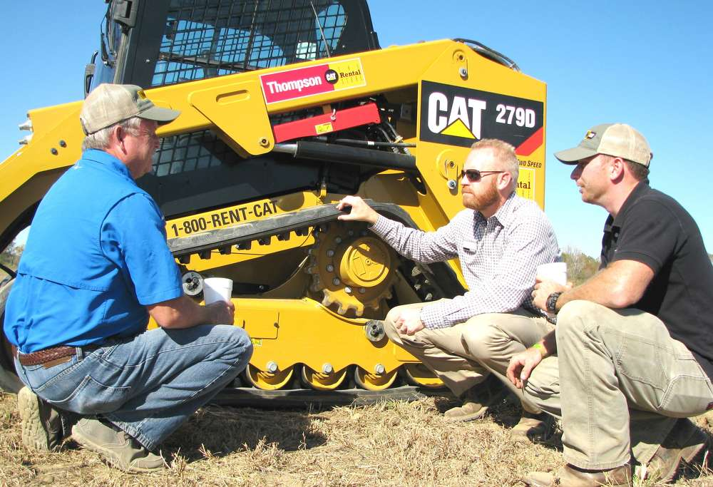 (L-R): Robert Hogue, Lumberjack Logging, New Albany, Miss.; Adam Ackerman, Caterpillar, Nashville, Tenn.; and Jason Hogue, also of Lumberjack Logging, discuss the track system on the Cat 279D compact track loader.