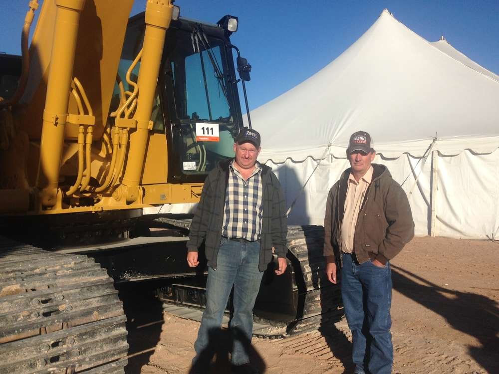 Gerardo Locusen (L) and Peter Franz came from Chihuahua, Mexico, to bid on the Cat 330B excavator pictured here. Locusen operates DGA Transport, a heavy equipment transport company.