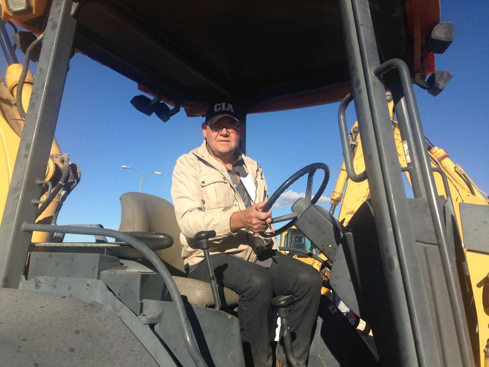 The auction featured many backhoe loaders. Jorge Arambula of El Paso's Power Concrete checks out a Deere 310G.