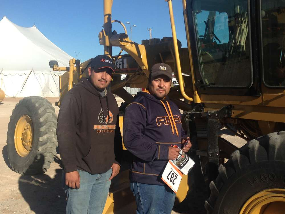 Allan Barraza (L) and Jorge Chavez represented Leopardo Truck Parts of El Paso, Texas. They were interested in this Cat 135H motorgrader.