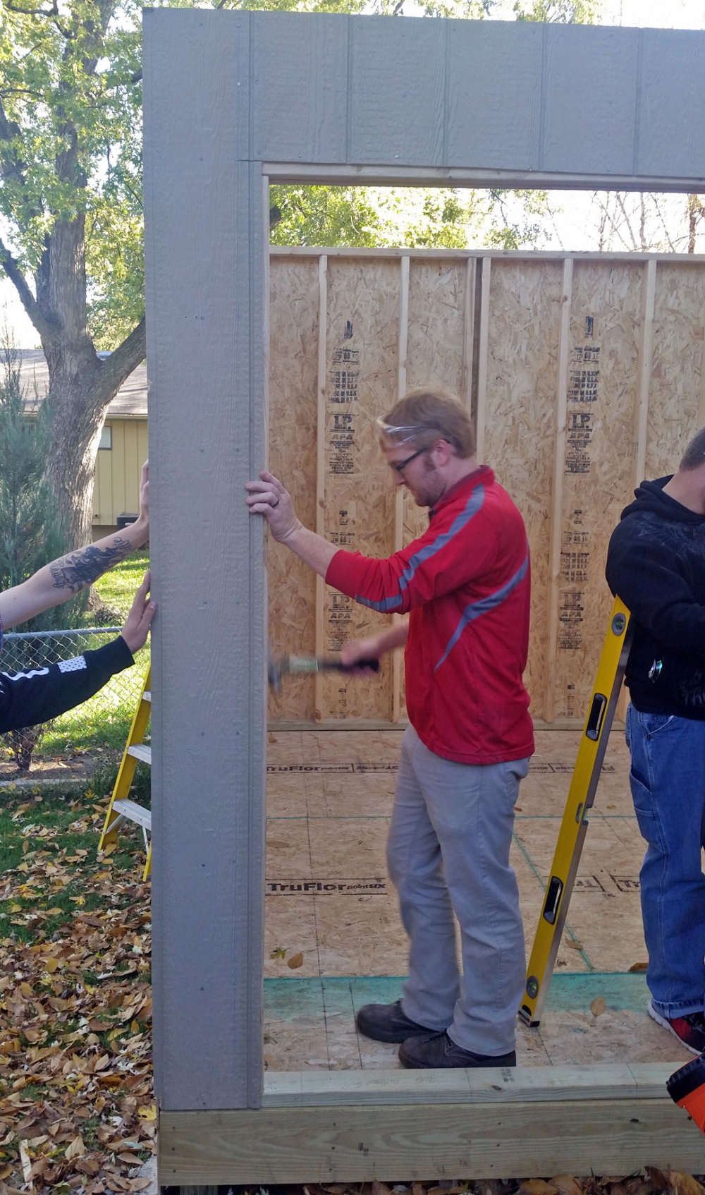 Ralston High School advanced woods and construction teacher Brandon Thoene helps put finishing touches on a shed his class built and delivered on Nov. 3.