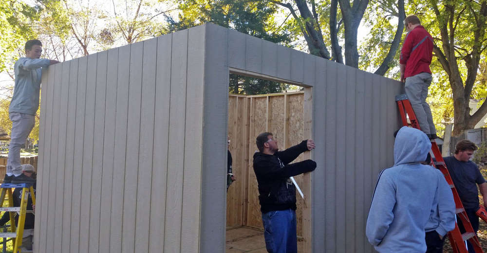 Students in the Ralston High School advanced woods and construction class assemble a shed that they constructed in class. The students framed and sided the side walls before delivering and assembling them on Nov. 3.