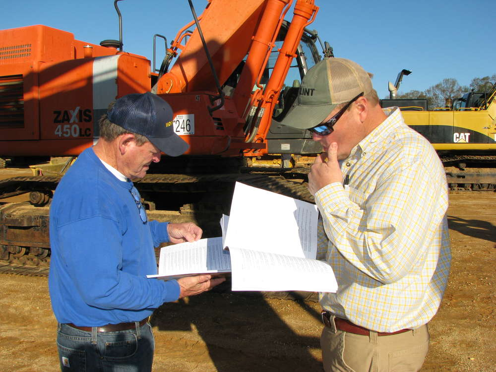 Bronson (L) and Todd Nichols, both of Bronson Nichols Construction, Andalusia, Ala., read up on the  machines they plan to bid on.